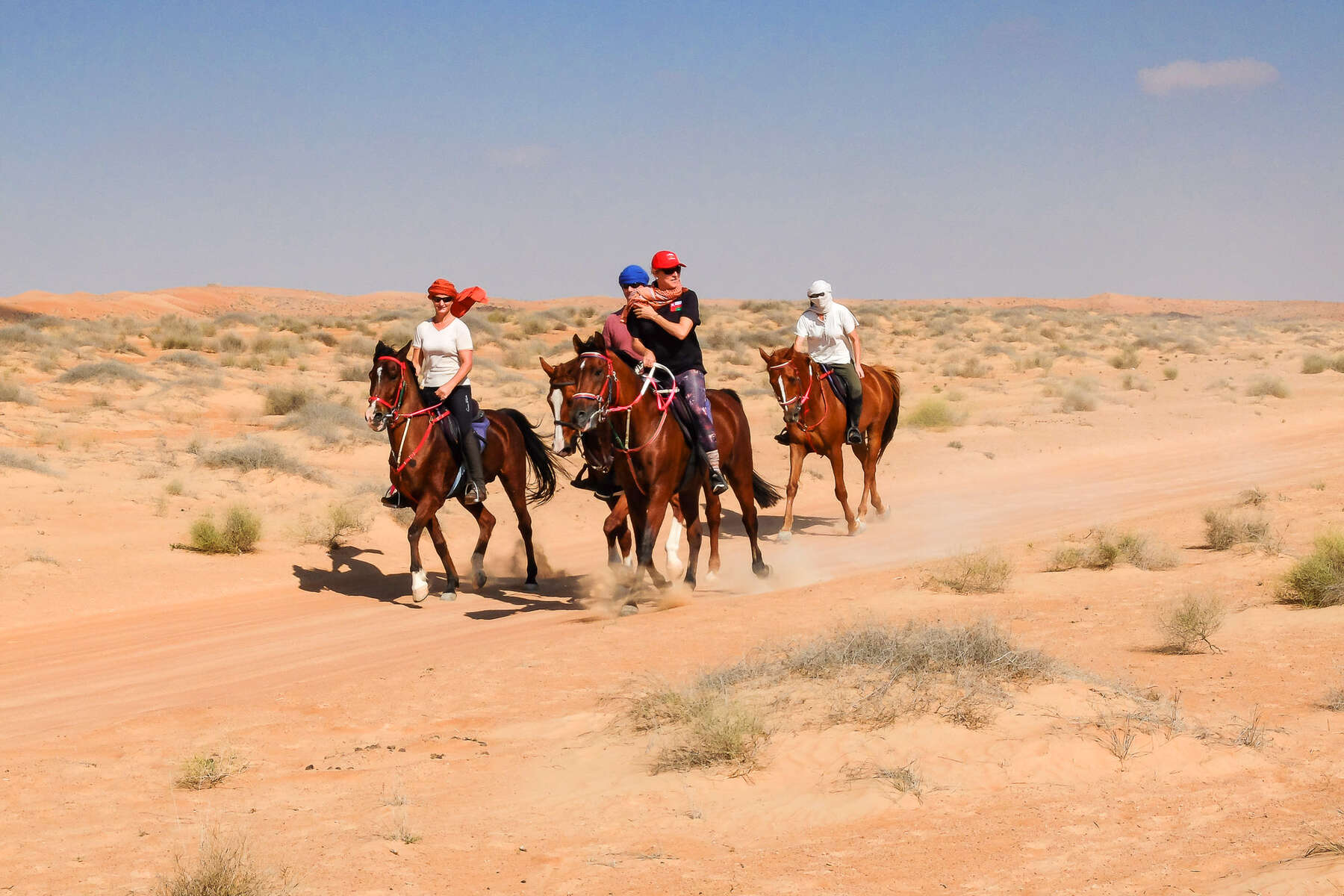 A group of riders in the Arabian desert