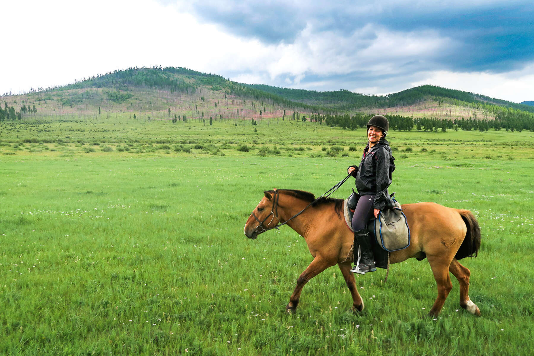 A rider smiling at the camera in Mongolia