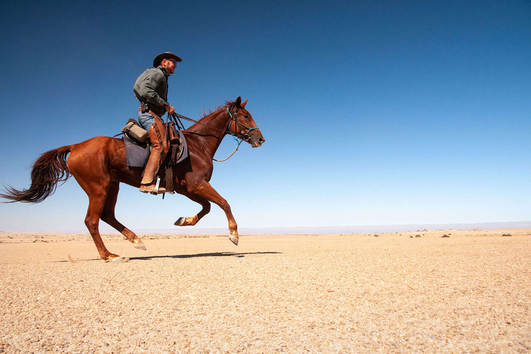 Andrew Gillies riding a horse in the Namib desert