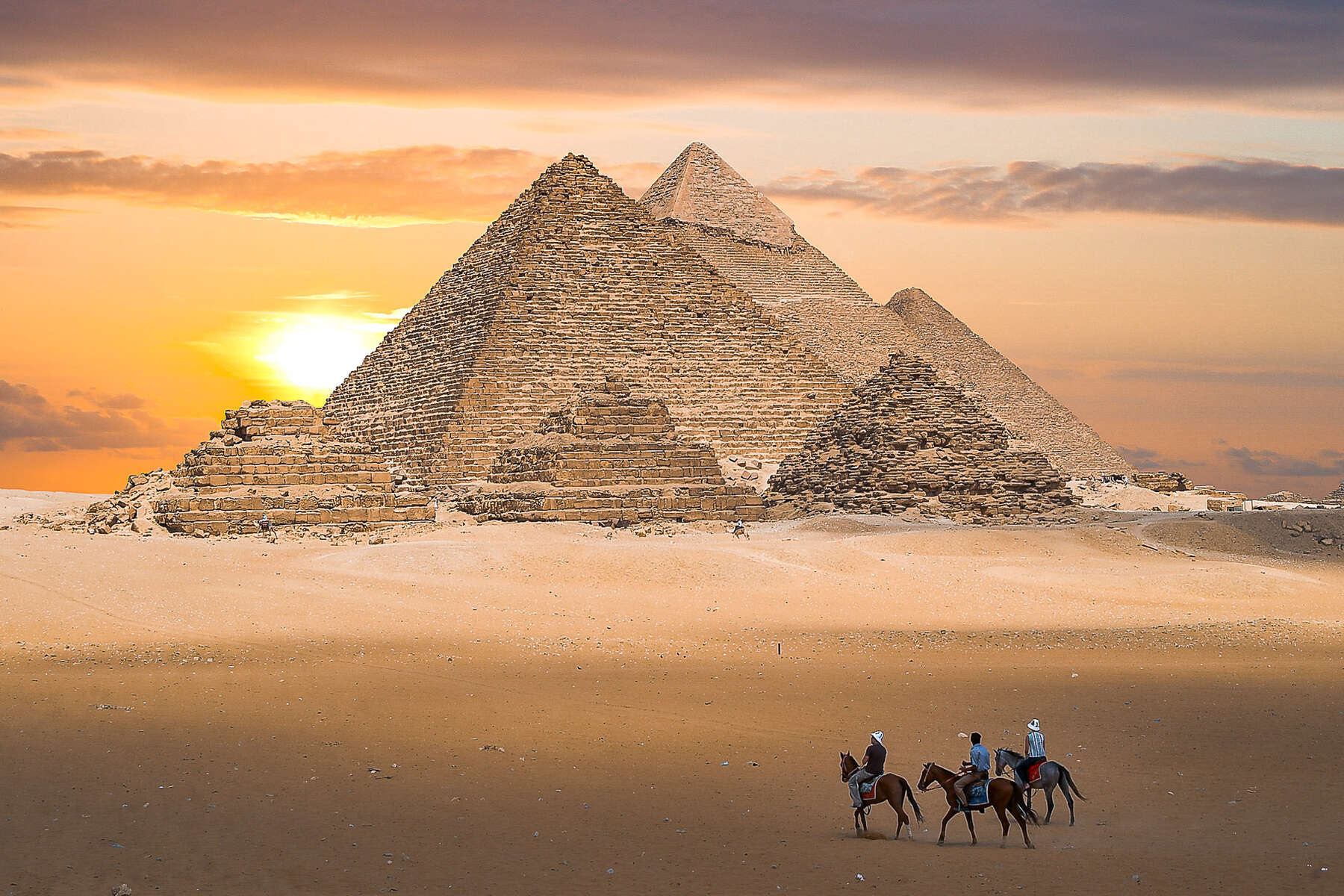 Riders approaching the pyramids in Egypt