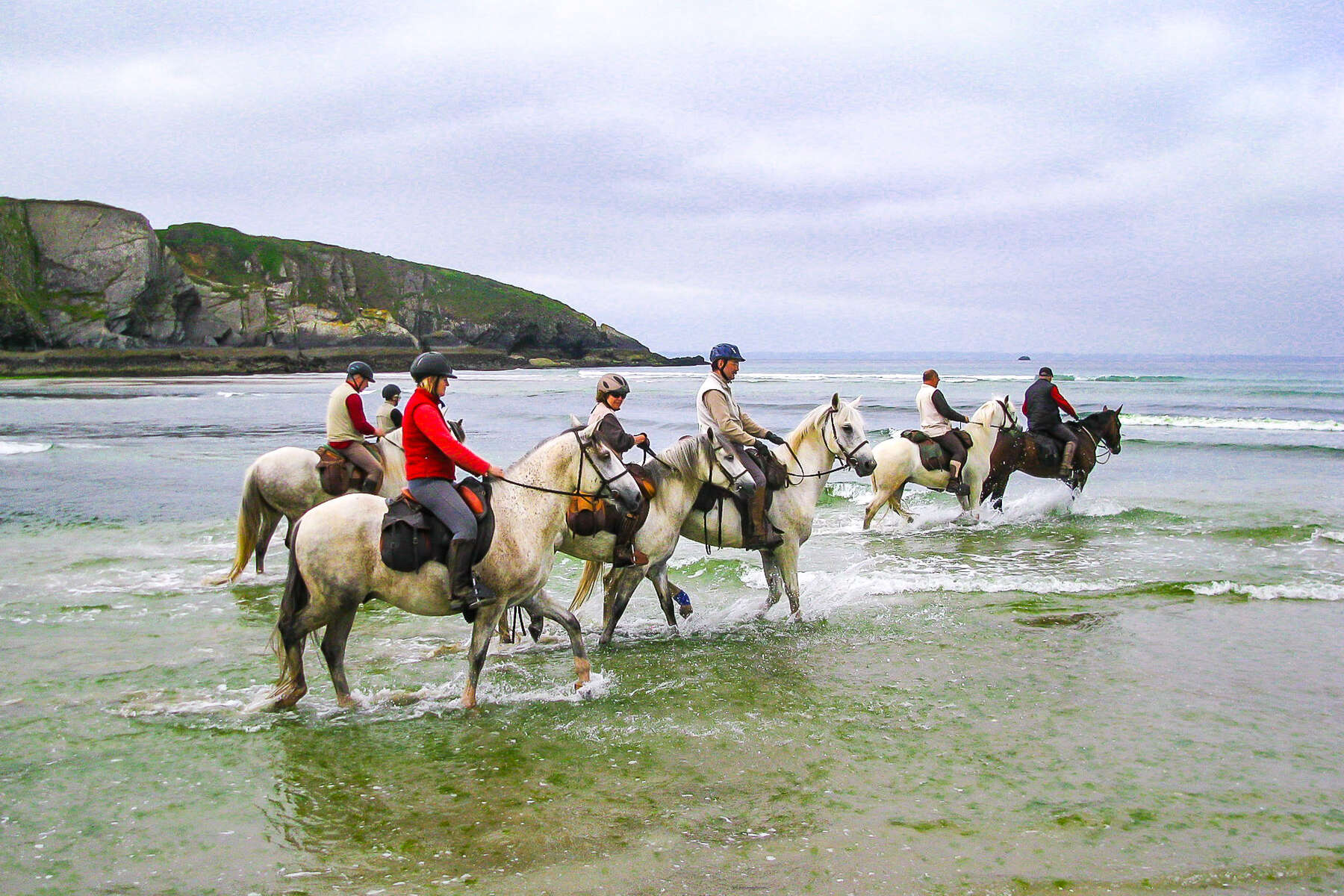 Riders riding their horses into the ocean in France