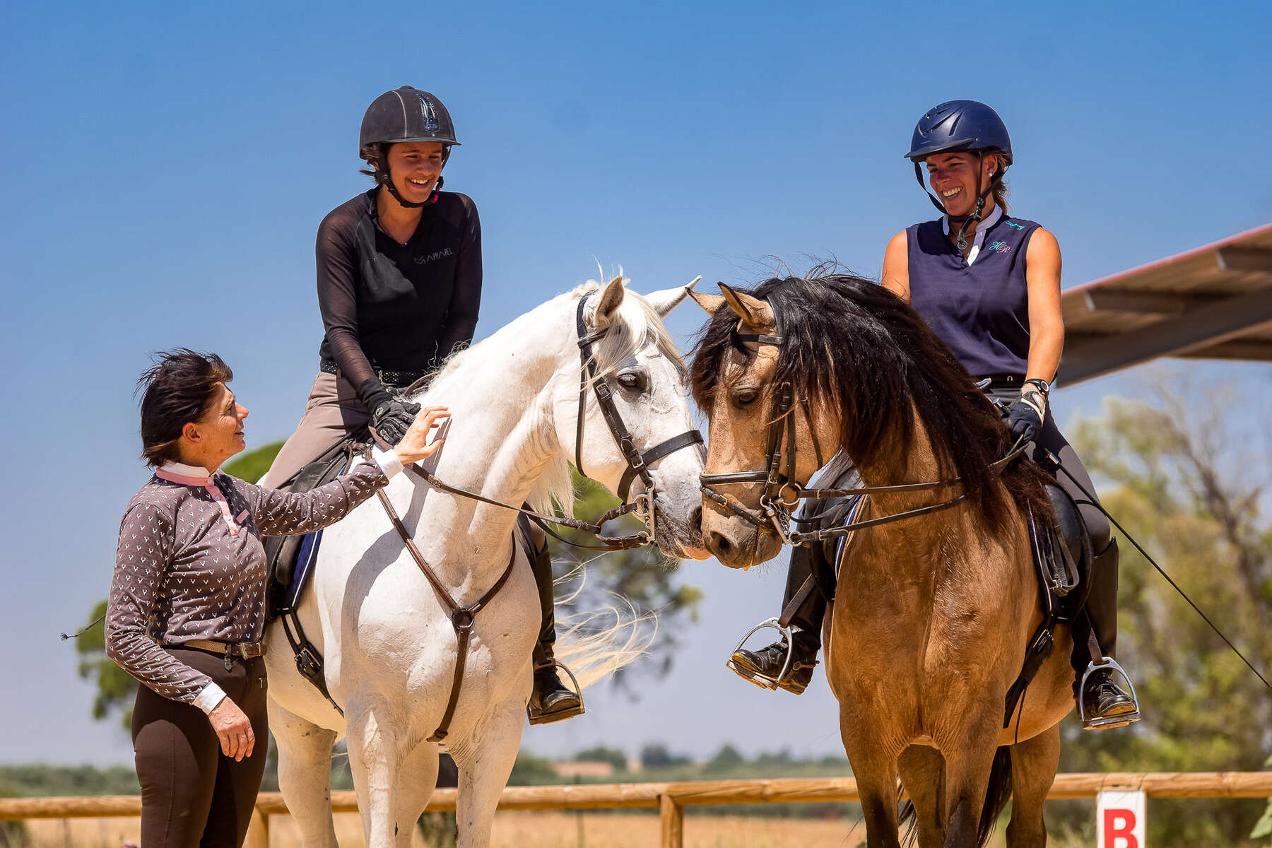 Two riders discussing with their instructors on a dressage holiday