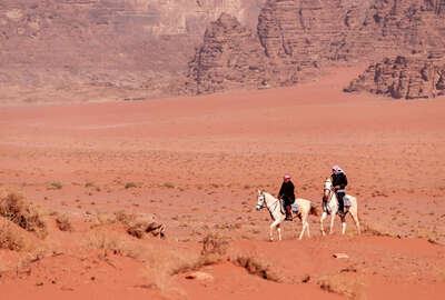 Horses and riders in the Wadi Rum desert, Jordan