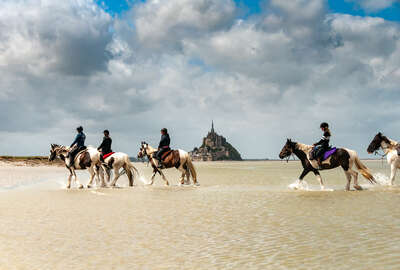 Horses and riders walking in the Ocean by Mt St Michel