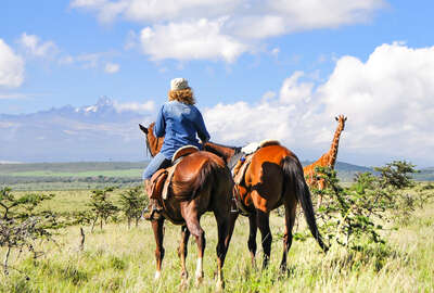 Rider at Borana Lodge and Conservancy watching giraffe on horseback