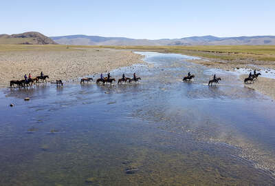 Riders crossing a river on horseback in mongolia