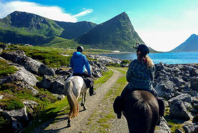 Riders riding in the Lofoten islands with a beautiful mountainous scenery