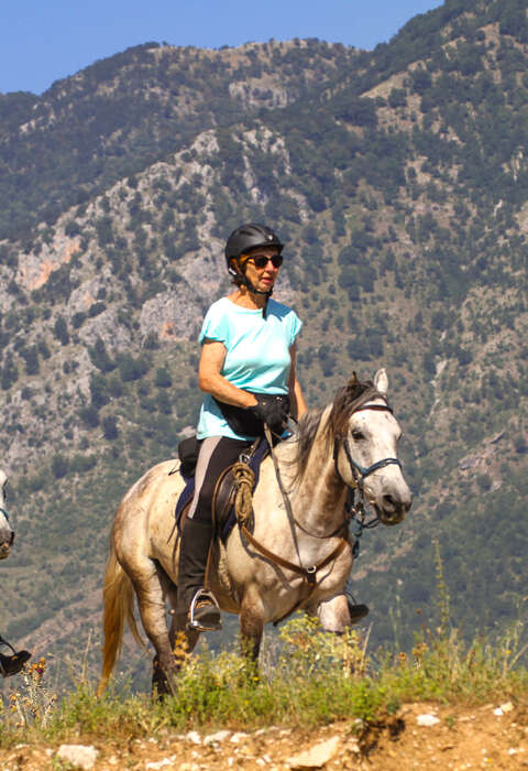 Horseback riders on a mountain trail ride in Albania