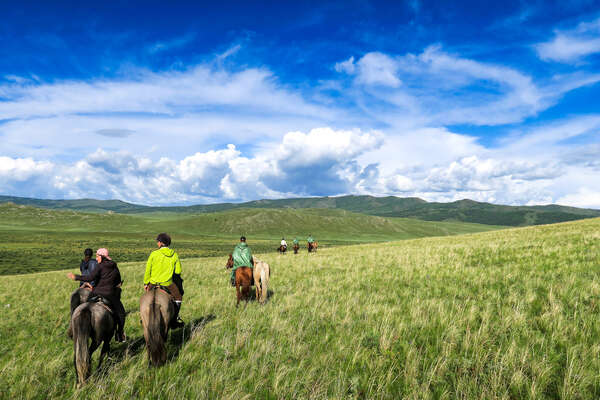 A group of riders riding across Khentii in Mongolia