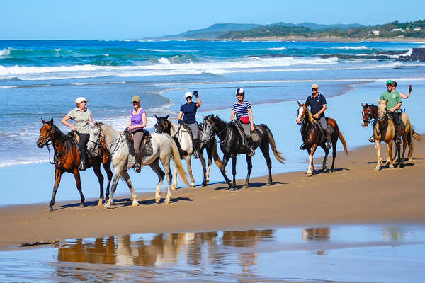 A group of riding on the beach, in South Africa