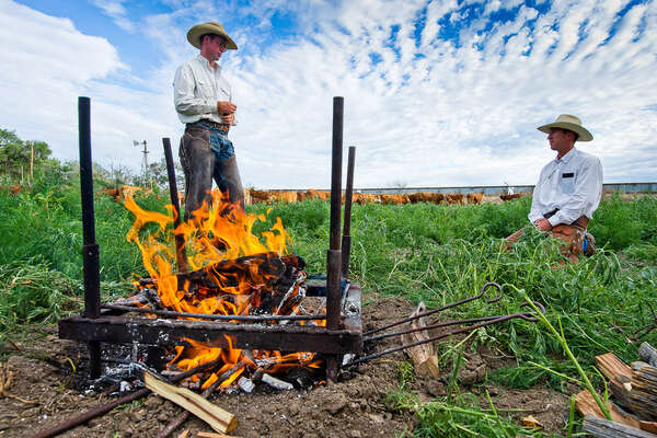 Cowboys getting the firepit ready for a branding day at Chico Basin ranch, Colorado