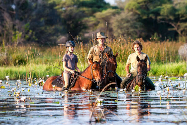 Family of riders in the floodplains of the Okavango delta