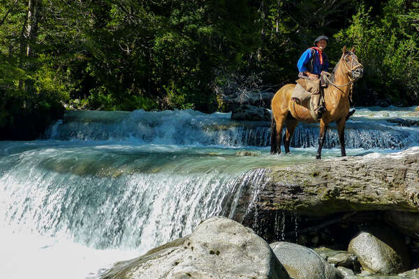Gaucho and horse in front of a river in the Andes