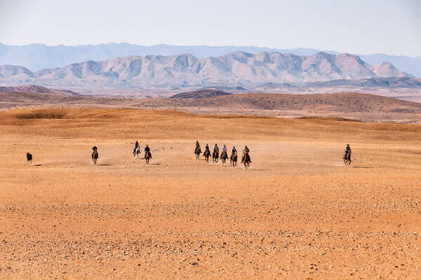 Group of riders cantering against the backdrop of the Namib