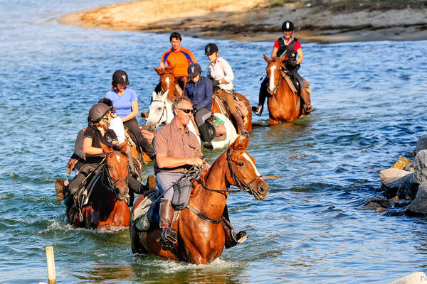 Group of riders riding in the Ocean in Mimizan