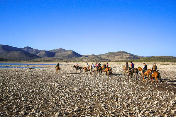 Groups of riders on horseback on a wide beach with mountains in the background