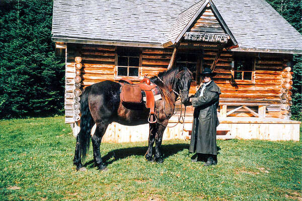Horse and rider in front of a wooden cabin in Canada