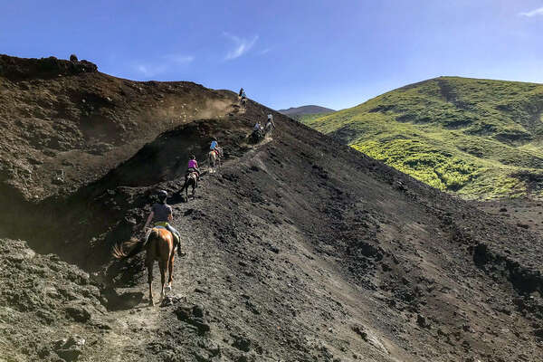 Horseback riders climbing the foothills of Mt Etna