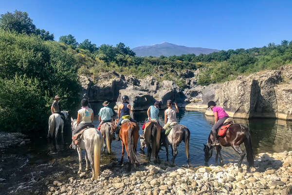 Horseback riders giving their horses a drink in Italy