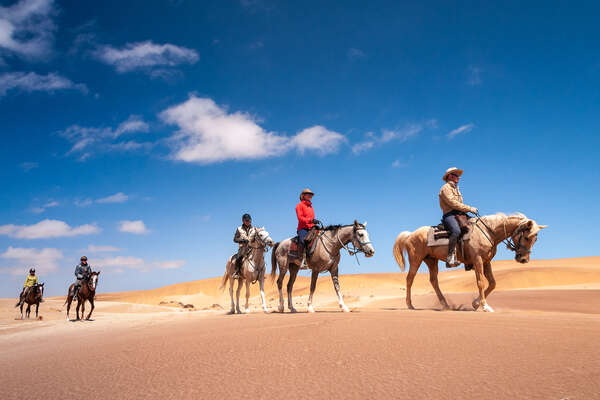 Horseback riders in the desert of Namibia