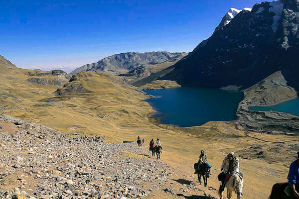 Horseback riding across the mountain range in Peru