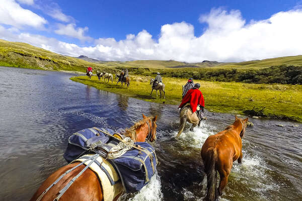 Horses and riders crossing a river in the Andes