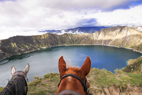 Horses in front of the Quilotoa crater lake in Ecuador