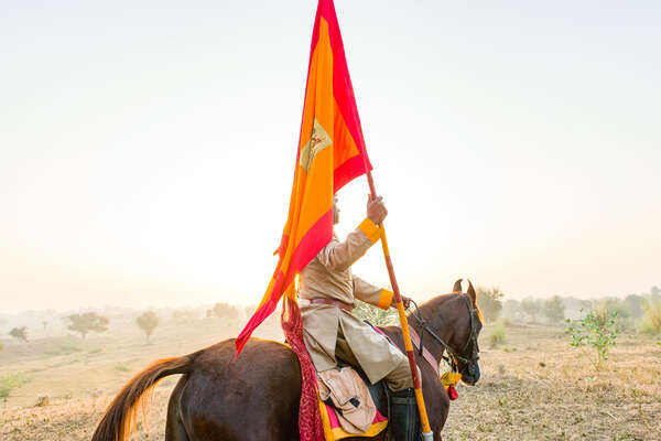 Indian riding carrying a flag and on  horseback
