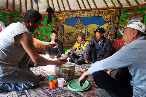 Nomads welcoming visitors to their yurt