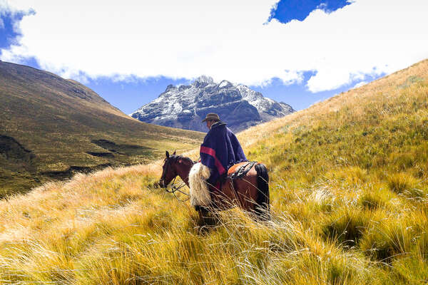 Rider on horseback in mountainous scenery in Ecuador