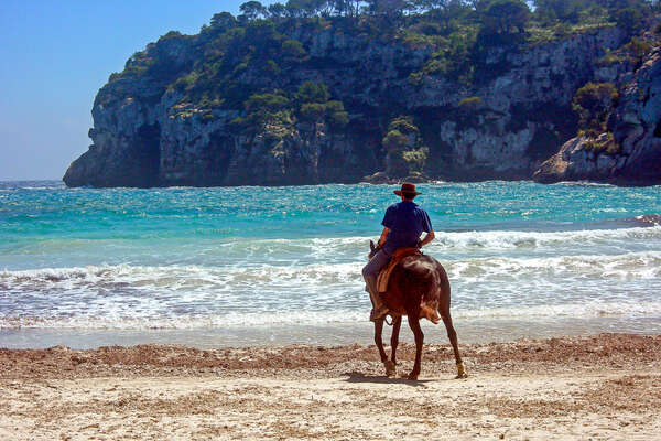 Rider riding his horse into the Mediterranean in Spain