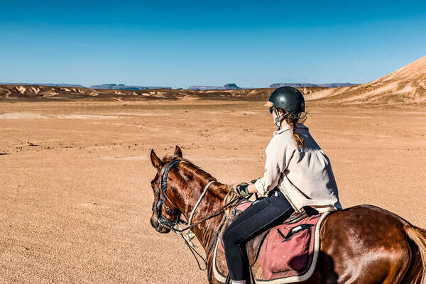 Rider riding through canyons in the Sahara in Morocco