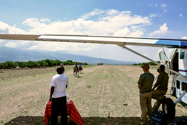 Riders cantering on an airplane track in Tanzania
