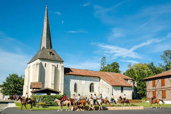 Riders crossing a French village in the landes on horseback