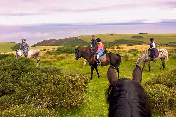 Riders enjoying a trail ride in Exmoor NP, with a view of the sea