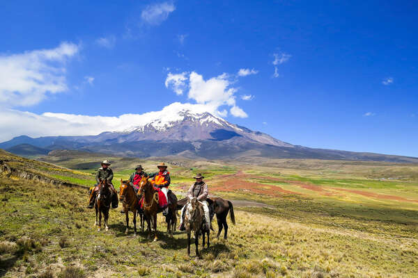 Riders in front of Cotopaxi volcano in Ecuador