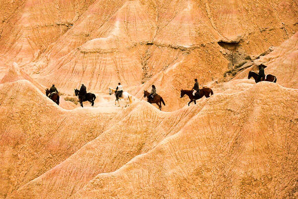 Riders in the Bardenas desert in Spain