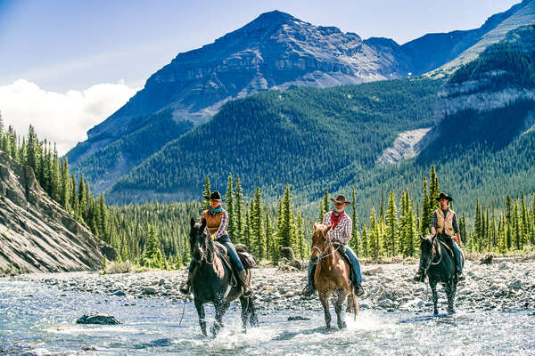 Riders in the river with a spectacular mountainous backdrop