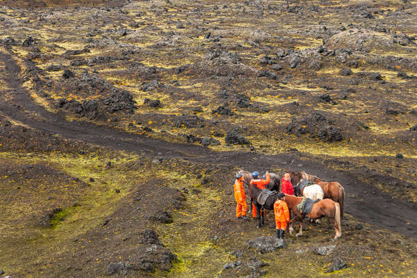 Riders on foot next to their horses in Landmannalaugar