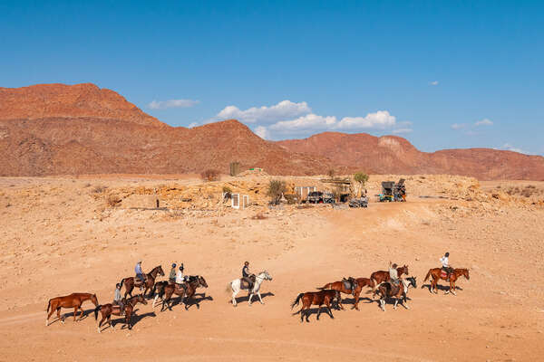 Riders on horseback in the Namib desert