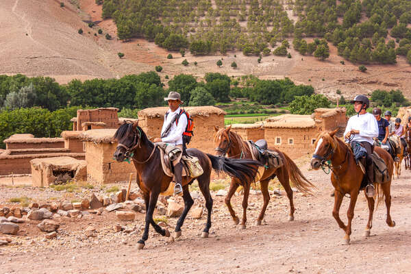 Riders riding across a traditional village in Morocco