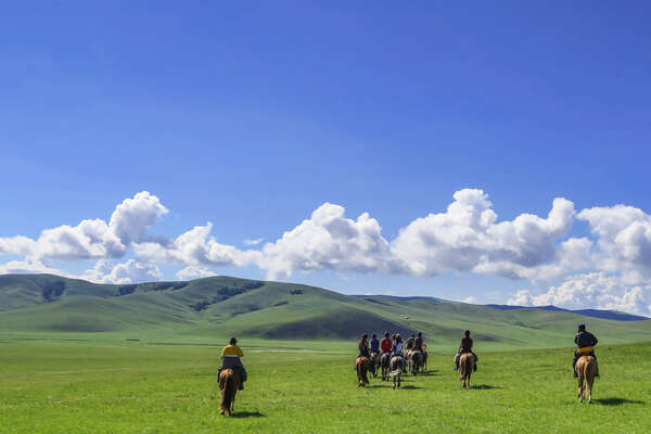 Riders riding across the steppe in the Khentii region of Mongolia