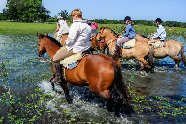 Riders riding horses in water, Uruguay