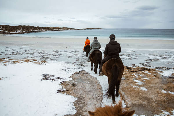 Riders riding in the beach with a snowy background in Gimsøy