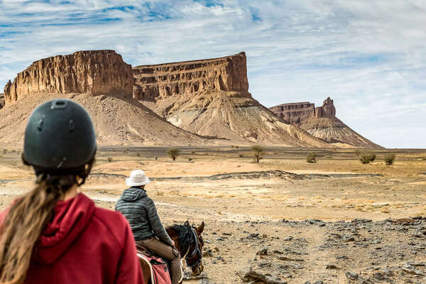 Riders riding out towards mountains in the Sahara