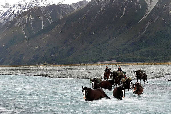 River crossing on horseback in New Zealand