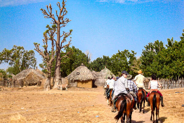 Senegal trail riders entering a village