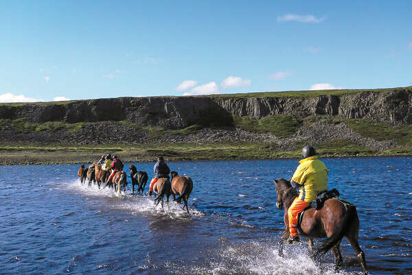 Small group of riders riding their horses in a river in Iceland