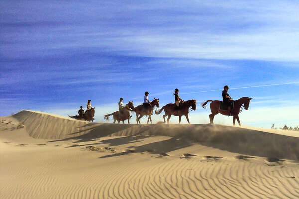 Trail riders in the sand dunes of Sardinia on horseback