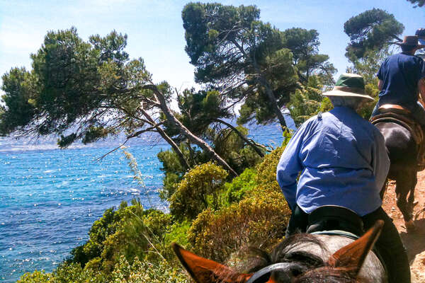 Trail riders riding along the coast in menorca